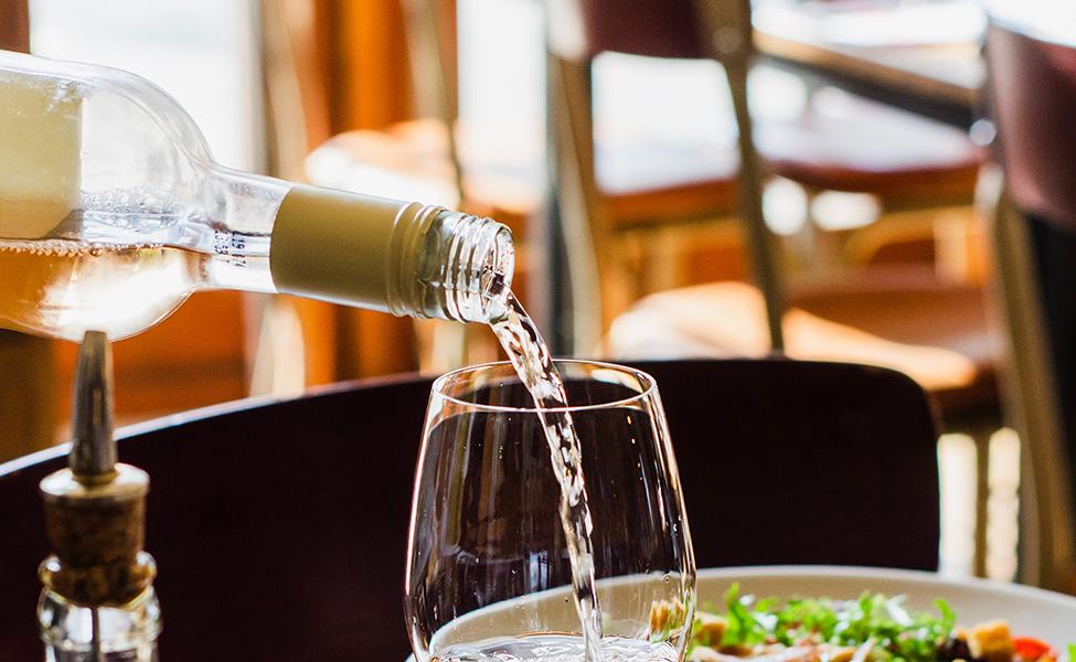 Belo vino koje se sipa u vinsku čašu u salonu