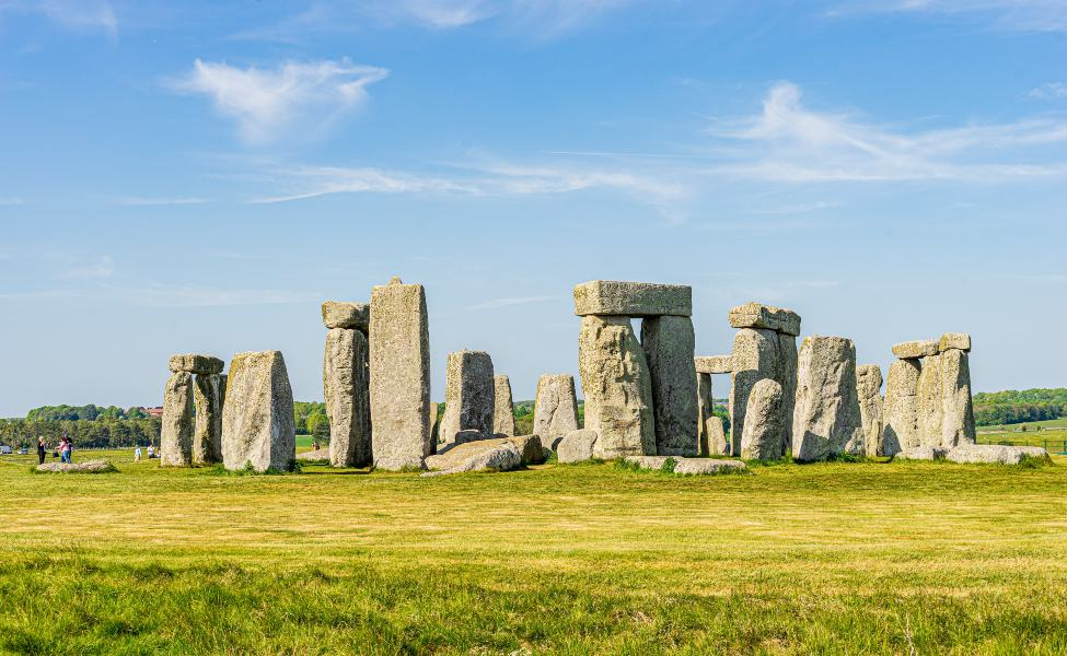 The monoliths of Stonehenge on a bright green field of grass