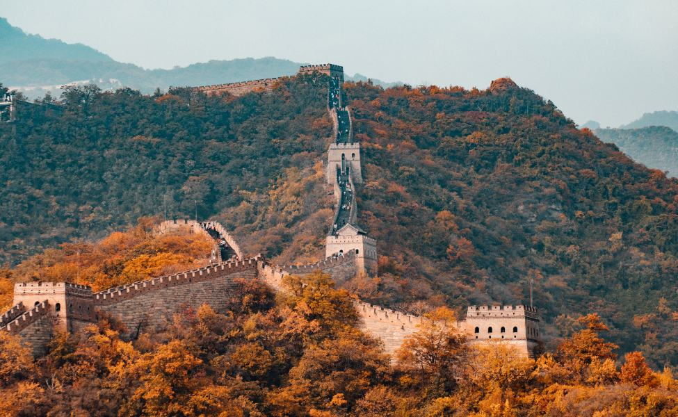 The Great Wall of China slithers through the autumnal woods