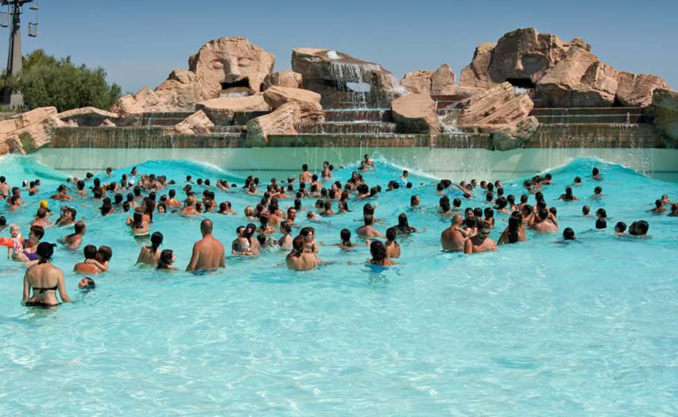 A crowd in a wavy pool decorated by the Mayan sculptures