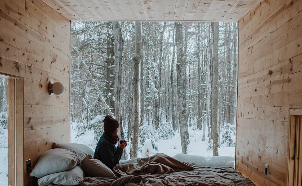 Devojka uživa u svom smeštaju gledajući kako sneg pada