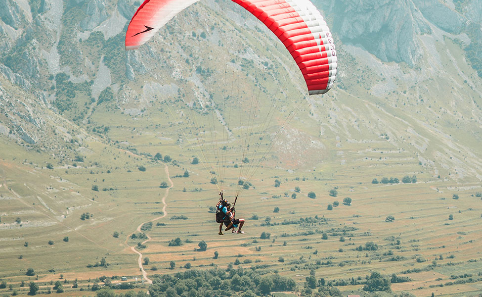 A guy that is flying above hills