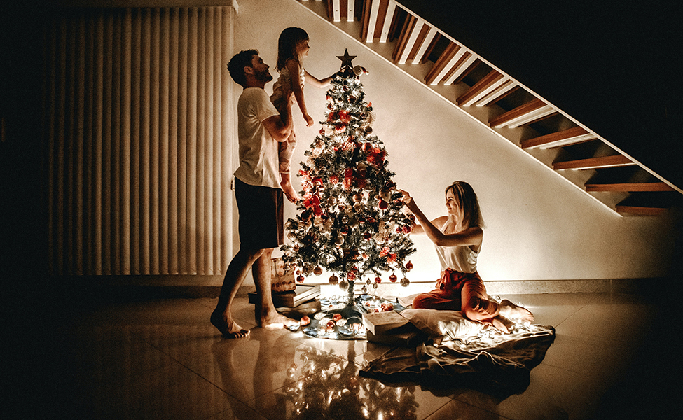 family decorating a Christmas tree with ornaments