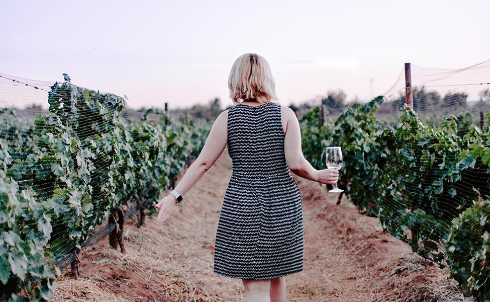 Devojka ide kroz vinograde